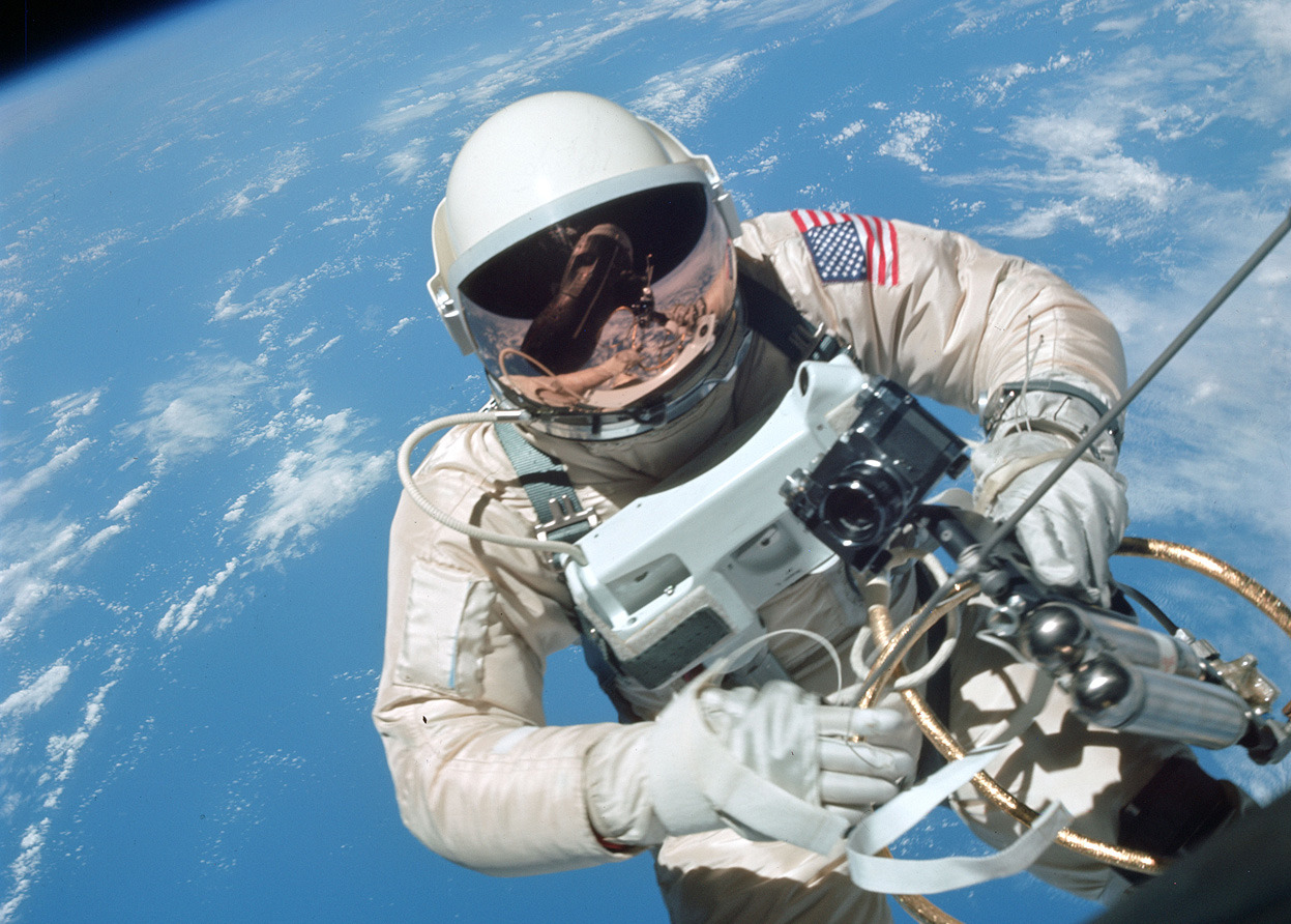From Remembering Project Gemini, one of 41 photos. NASA Astronaut Edward White floats in zero gravity of space northeast of Hawaii, on June 3, 1965, during the flight of Gemini IV. White is attached to his spacecraft by a 25-ft. umbilical line and a 23-ft. tether line,both wrapped in gold tape to form one cord. In his right hand he carries a Hand-Held Self-Maneuvering Unit. (NASA/JSC/ASU)