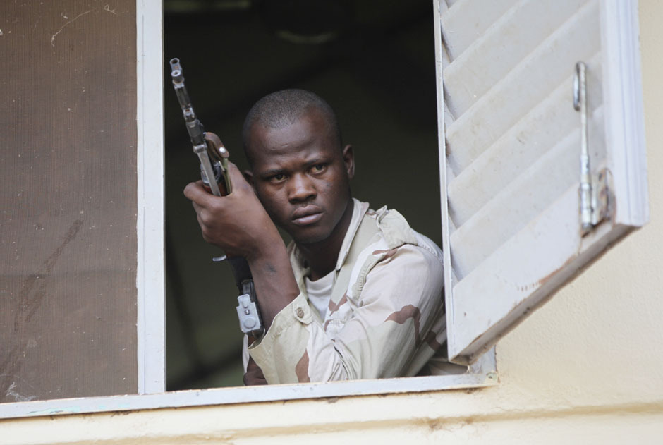 A Malian junta soldier holds a gun as he stands guard in the headquarters in Kati, outside Bamako, Mali April 3, 2012. [Credit : Luc Gnago/Reuters]