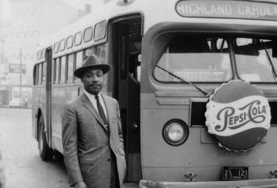 Dr. Martin Luther King, Jr. stands in front of a bus at the end of the Montgomery Bus Boycott in Alabama (December 26, 1956).  The boycott was a political and social protest against racial segregation on Montgomery's public transportation system.  At the time, white people who boarded the bus took seats in the front rows and black people took seats in the back rows. If the bus was full and another  white person boarded the bus, then the black passengers closest to the front had to offer their seat. Often when boarding the buses, black people were required to pay at the front, get off, and reenter the bus through a separate door at the back. On some occasions bus drivers would drive away before black passengers were able to re-board. Today (4/4/12) is the anniversary of Dr. Martin Luther King, Jr.'s assassination in Memphis, Tennessee.Please take a moment on your bus or train ride home to remember his and other civil right leaders fight to make America's public transit systems equally accessible to all.  Photo credit: The History Channel (History.com)