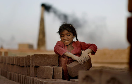 fotojournalismus:  Naginah Sadiq, five, lays bricks at the brick factory where she and her family work. Naginah earns 250 rupees (£1.74) per day according to her father in Islamabad, Pakistan, April 4, 2012. [Credit : Muhammed Muheisen/AP]