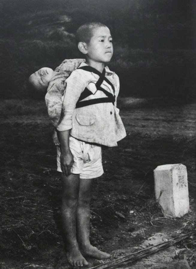 "Real-life Grave of the Fireflies: (Photo) Stoic Japanese orphan, standing at attention having brought his dead younger brother to a cremation pyre, Nagasaki, by Joe O'Donnell 1945  This photograph was taken by an American photojournalist, Joe O'Donnell, in Nagasaki in 1945. He recently spoke to a Japanese interviewer about this picture:  ""I saw a boy about ten years old walking by. He was carrying a baby on his back. In those days in Japan, we often saw children playing with their little brothers or sisters on their backs, but this boy was clearly different. I could see that he had come to this place for a serious reason. He was wearing no shoes. His face was hard. The little head was tipped back as if the baby were fast asleep. ""The boy stood there for five or ten minutes. The men in white masks walked over to him and quietly began to take off the rope that was holding the baby. That is when I saw that the baby was already dead. The men held the body by the hands and feet and placed it on the fire. ""The boy stood there straight without moving, watching the flames. He was biting his lower lip so hard that it shone with blood. The flame burned low like the sun going down. The boy turned around and walked silently away."