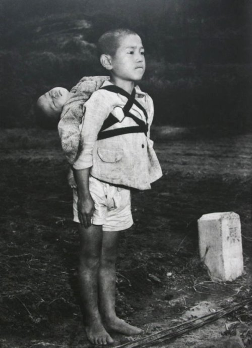 "ace-su:  Real-life Grave of the Fireflies: (Photo) Stoic Japanese orphan, standing at attention having brought his dead younger brother to a cremation pyre, Nagasaki, by Joe O'Donnell 1945  This photograph was taken by an American photojournalist, Joe O'Donnell, in Nagasaki in 1945. He recently spoke to a Japanese interviewer about this picture:  ""I saw a boy about ten years old walking by. He was carrying a baby on his back. In those days in Japan, we often saw children playing with their little brothers or sisters on their backs, but this boy was clearly different. I could see that he had come to this place for a serious reason. He was wearing no shoes. His face was hard. The little head was tipped back as if the baby were fast asleep. ""The boy stood there for five or ten minutes. The men in white masks walked over to him and quietly began to take off the rope that was holding the baby. That is when I saw that the baby was already dead. The men held the body by the hands and feet and placed it on the fire. ""The boy stood there straight without moving, watching the flames. He was biting his lower lip so hard that it shone with blood. The flame burned low like the sun going down. The boy turned around and walked silently away.""   This has been one of the most depressing things I have read. (And I am most ashamed to say all this time I thought the characters from Grave of the Fireflies were fictional. For goodness' sake, the movie was based on a semi-autobiography. As a kid I never really liked that movie given its atmosphere, and now, knowing this just made it more disturbing and depressing.)"