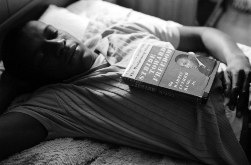 © Paul Schutzer, 1961, Montgomery, Alabama 'A Freedom Rider sleeps at a safe house, his copy of Dr. King's Stride Toward Freedom close at hand.' It's mid-spring, 1961. In the kitchen of a safe house in Montgomery, Alabama, Dr. Martin Luther King Jr. is tense. In the house with the 32-year-old civil rights leader are 17 students — fresh-faced college kids who, moved by King's message of racial equality, are literally putting their lives at risk. These are the groundbreaking practitioners of nonviolent civil disobedience known as the Freedom Riders, and over the past two harrowing weeks, as they've traveled across the state on integrated buses, their numbers have diminished at every stop in the face of arrests, mob beatings, and even fire-bombings. » see pictures of Martin Luther King, Jr. here «