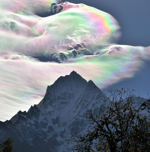 This is a cloud over the Himalayas. The rainbow-like colors could be coming from refraction of light through water vapor in the clouds. My eyes are drawn to the lighter colors at the top of the photo, instead of the darker ones at the bottom.