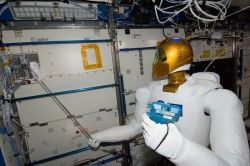 "Controlled from the ground, NASA's Robonaut 2 holds an instrument for measuring air velocity aboard the International Space Station on March 14. The robotic astronaut was handling the device as part of a series of dexterity tests, which included spelling out ""Hello, world"" in sign language."