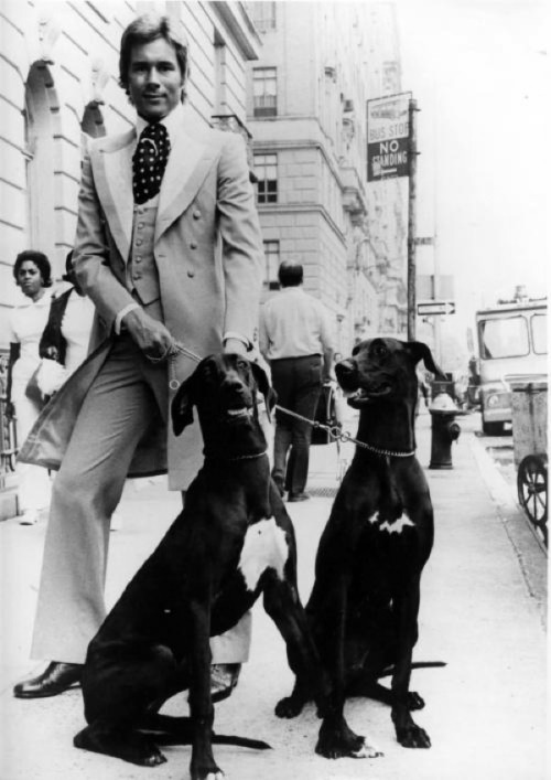 "naturalbornworldshakers:  The flamboyantly natty Savile Row tailor Tommy Nutter with his dogs. ""Although tailoring was quite distinct from fashion then, Tommy Nutter changed the way men dressed,"" says Dennis Nothdruft, who co-curated the 2011 retrospective (Tommy Nutter: Rebel on the Row) at the Fashion and Textile Museum in London along with tailor Timothy Everest. ""And he changed the way Savile Row was seen. Before Nutters it was an exclusive, closed-off world. They didn't even have window displays. Though, of course, the rest of the row looked upon him as an upstart whose shop was on the wrong side of the street."" (The huge purple candles in the shape of phalluses can't exactly have endeared him to his neighbors… Another legend, Simon Doonan, was Nutter's window dresser back in those days.) Read more…"