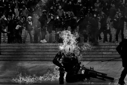 Photographing Greek Protests The New York Times Lens Blog profiles Angelos Tzortzinis, a 28-year-old Greek photographer who's been shooting his country's protests over austerity measures. His ideal shooting location, he says, is between the protestors and the police. Via the New York Times:  Taking photos during demonstrations in Athens can be very difficult — tear gas clouds create a suffocating atmosphere, people without gas masks run in all directions, while protesters who have masks hurl stones and Molotov cocktails. To get his pictures, Mr. Tzortzinis says he must stand between the riot police and the protesters, every moment exposed to violence from either side. Many times photographers have been attacked by the riot police. But many times, too, they have lost their equipment after being attacked by angry protesters.  Image: A riot officer after being hit with a Molotov Cocktail, by Angelos Tzortzinis. Via the New York Times. Tzortzinis' work can be seen the Times' link above as well as on his personal site.