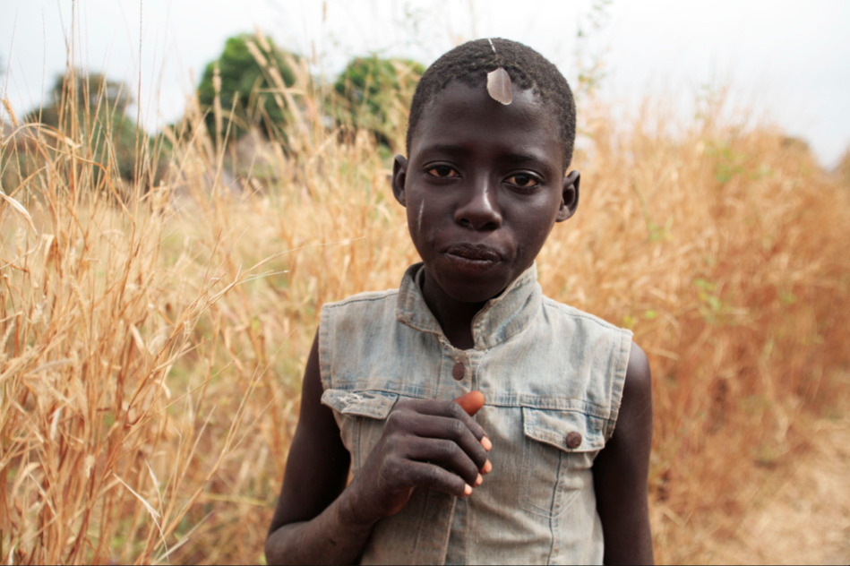 Random Road Shots: Gambian boy with feather in his hair Taken whilst on 'A Short Walk in The Gambian Bush - a 930km African odyssey' - 2009 - The Gambia, West Africa Image © Jason Florio