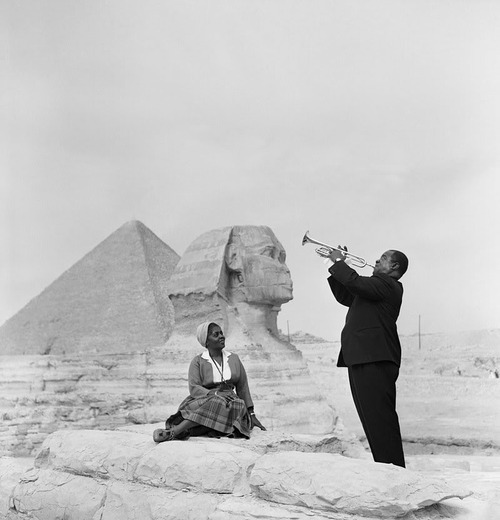 prodigiousbirth:  Louis Armstrong playing for his wife in front of the Sphinx in Cairo, Egypt.  ما تلعب في بلدكو يا عم :D