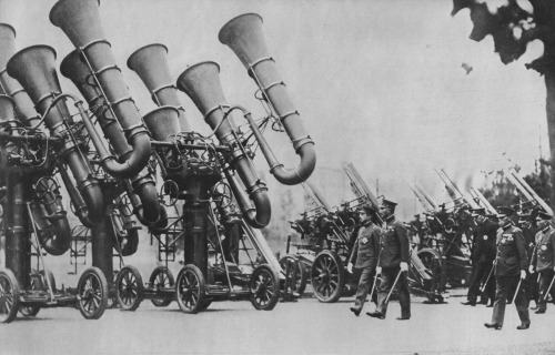 (via Airminded · Future schemes of air defence) MONSTER EAR TRUMPETS FOR AIR DEFENCE  During the last years of the Great War, sound detectors played an increasingly important part in the air defences of all the belligerents. Since those days they have undergone great development. Here the emperor of Japan is inspecting the huge trumpet-like detectors that work in conjunction with the anti-aircraft guns (seen right)