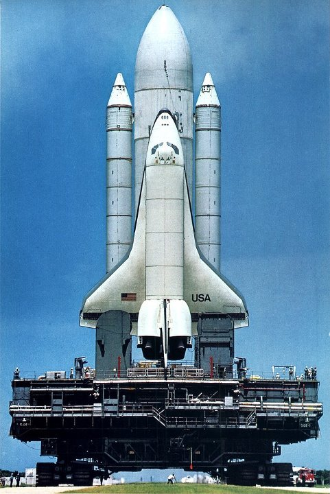 After a two-year delay, the space shuttle Columbia is posed for launch this spring from Cape Canaveral. Photo by Jon Schneeberger, National Geographic, Vol. 159, No. 3, March 1981. Note the tiny tiny photographer between the caterpillars of the crawler-transporter.