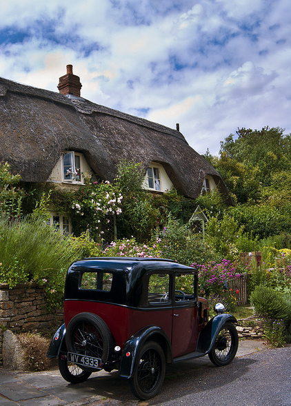 joilieder:  Thatched cottage and vintage car in Lacock, Wiltshire, England.  The village of Lacock is mostly owned by the National Trust.  The village has been used in films and movies due to its old world charm.