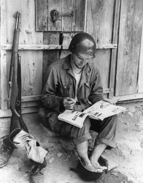 An American soldier relaxes by taking a footbath in a spare helmet whilst reading a magazine, during the Korean War, 1950.