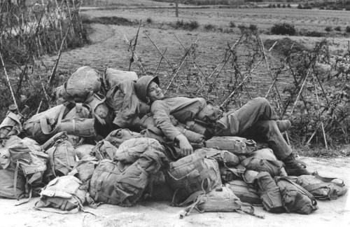 An American soldier relaxing on a heap of kit-bags, shortly after the invasion and capture of the Korean port of Inchon, 1950.