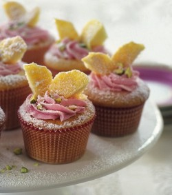 Rose and Vanilla Cupcakes  Ingredients 1 1/2 cups self-rising flour 2 pinches of salt 20 Tbs. (2 1/2 sticks) unsalted butter, at room temperature 3/4 cup granulated sugar 4 1/2 tsp. plus 1 Tbs. rose water 2 1/2 tsp. vanilla extract 3 eggs, lightly beaten 3 cups confectioners' sugar, sifted, plus more for dusting (optional) 3 drops pink food coloring 2 Tbs. finely chopped pistachio nuts Preheat an oven to 350ºF. Line a 12-cup muffin pan with paper liners. Method Sift the flour and 1 pinch of salt into a small bowl. Set aside. In the bowl of a stand mixer fitted with the flat beater, beat together 12 Tbs. (1 1/2 sticks) of the butter and the granulated sugar on medium-high speed until light and fluffy, scraping down the sides of the bowl as needed. Add the 4 1/2 tsp. rose water and 1 1/2 tsp. of the vanilla. Reduce the speed to medium and add the eggs one at a time, scraping down the sides of the bowl and making sure each egg is fully incorporated before adding the next one. Reduce the speed to low, gradually add the flour mixture and beat until just incorporated. Divide the batter evenly among the prepared muffin cups. Bake until the cupcakes are golden and a toothpick inserted in the center of a cupcake comes out clean, 15 to 20 minutes. Transfer the pan to a wire rack and let the cupcakes cool completely. Meanwhile, make the buttercream: In the bowl of the stand mixer fitted with the flat beater, beat together the remaining 8 Tbs. (1 stick) butter, the 3 cups confectioners' sugar and 1 pinch of salt until smooth. Mix in the 1 Tbs. rose water, the remaining 1 tsp. vanilla and a few drops of food coloring. Place the buttercream in a pastry bag fitted with a star tip. Using a small paring knife, cut a cone-shaped piece from the top of each cupcake. Each cone should be about 1 1/2 inches in diameter and about 1 inch long. Cut each cone in half lengthwise. These 2 pieces will be the wings for each cupcake. Pipe buttercream into the center and over the top of each cupcake. Insert the wings in the center, poking the tips into the frosting and turning the flat side of each piece outward. Sprinkle the cupcakes with pistachios, dust with confectioners' sugar and serve. Makes 12 cupcakes.