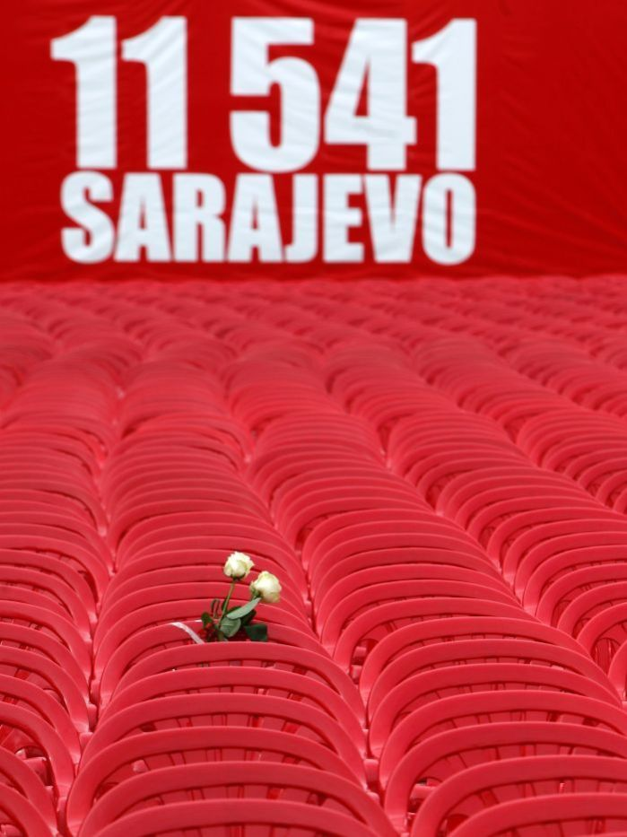 "fotojournalismus:  Red chairs are displayed along a main street in Sarajevo as the city marks the 20th anniversary of the start of the Bosnian war on April 6, 2012. Some 100,000 people died and 2 million people were forced from their homes as Bosnia gave the lexicon of war the term ""ethnic cleansing"". Slow-motion intervention eventually brought peace, but at the cost of ethnic segregation. In a blood-red symbol of loss, empty chairs stretched 800 meters down the central Sarajevo street named after socialist Yugoslavia's creator and ruler for 35 years, Josip Broz Tito. Smaller chairs represented the more than 600 children killed in the 43-month siege by Serb forces that held the hilltops. Thousands of people gathered for a concert in remembrance with a choir of 750 Sarajevo schoolchildren. Queuing for water or shopping at the market during the siege, Sarajevans were picked off by snipers and random shelling. Running out of burial places, many of the bodies were interred beneath a hillside football pitch. On Thursday, cellist Vedran Smailovic, who became an icon of artistic defiance when he played on a central Sarajevo street as the city was shelled, played again for the first time in his hometown since he left in 1993 as part of an exodus of thousands. [via] [Credit : Dado Ruvic/Reuters]"