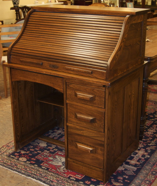 Impeccable single pedestal roll-top desk from around 1915 made of elm wood. This is an S roll tambour which is intact and functions like new. The lock on the tambour seems to have been removed a long time ago and the finish restored at some point in it's history.                                                   SOLD