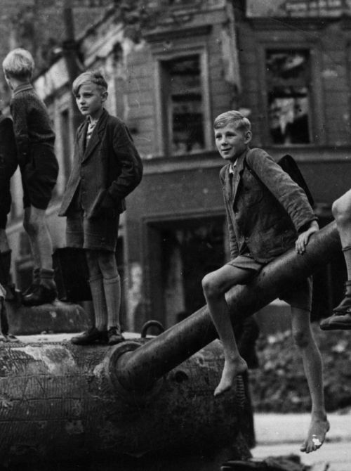 Children play on the bomb sites and wrecked tanks in Berlin, in the aftermath of the fighting in the city, 1945.