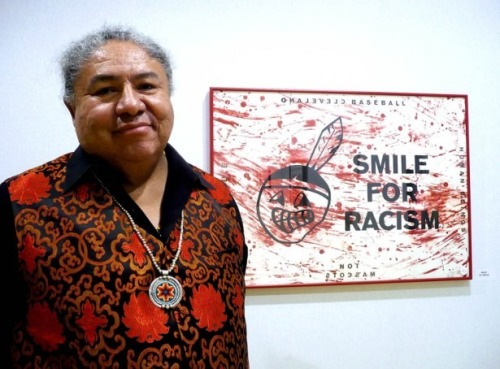 "tgstonebutch:   Heap of Birds, with his painting, ""Smile for Racism""  At a Native American art exhibit in Paris."