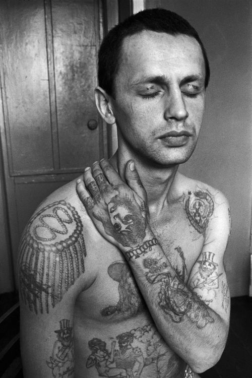 "Sergei Vasiliev RUSSIAN CRIMINAL TATTOO ARCHIVE ""The tattoos across the eyelids read 'Do not / Wake me'. The genie on the forearm is a common symbol of drug addiction. If an addict is imprisoned for drug offences, he or she will have to go through withdrawal in the 'zone' (prison). Epaulette tattoos (on the shoulders) display the criminal's rank in a system that mirrors that of the army (major, colonel, general etc)."""