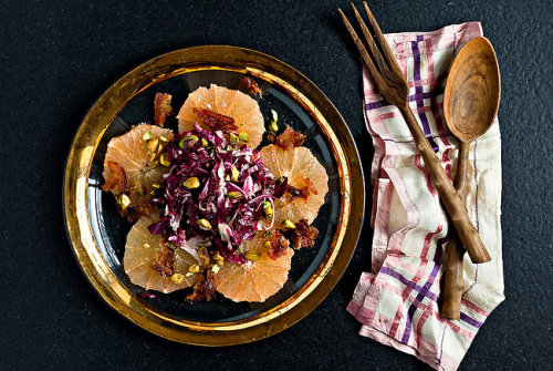 Pink Grapefruit and Radicchio Salad With Dates and Pistachios (via NYTimes Dining & Wine) 2 pink or red grapefruits 2 medjool dates, pitted and thinly sliced 1/2 medium shallot, peeled and thinly sliced Fine sea salt, to taste 1 small head radicchio, halved and cored 4 tablespoons extra-virgin olive oil 2 tablespoons coarsely chopped pistachio nuts Freshly ground black pepper.  1.  Slice the top and bottom off one of the grapefruits. Stand it up on a cut side and, using a small sharp knife, slice off the peel and pith, following the curve of the fruit. Save the peels (there should be some red fruit clinging to the pith). Repeat with the other grapefruit. Slice both grapefruits into quarter-inch-thick rounds and arrange on a platter. Evenly sprinkle the dates on top. 2.  Squeeze the juice from the grapefruit peel into a small bowl. You should have about a tablespoon. If there is less, squeeze some from one of the grapefruit slices. Add the shallot and a pinch of salt; let sit for 5 minutes. 3.  Meanwhile, thinly slice the radicchio and add to a bowl. Add the shallot and grapefruit juice and toss to combine. Toss in 3 tablespoons of the oil. 4.  Sprinkle grapefruit slices with salt and drizzle with the remaining oil. Place a mound of the radicchio in the middle of the grapefruit, leaving a border of the fruit exposed. Sprinkle with pistachios and black pepper and serve immediately. Yield: 4 servings.