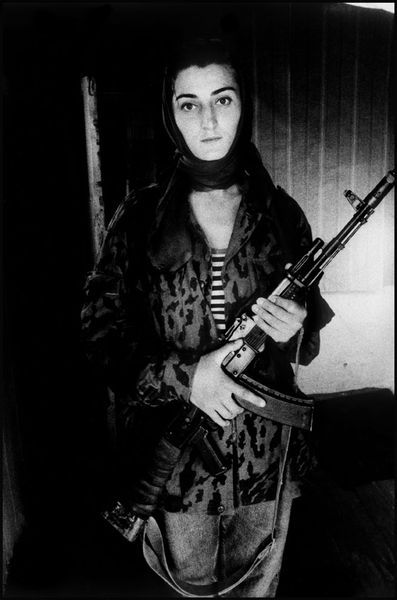 fotojournalismus:  Asya, a Chechen rebel, portrait of a woman. Now 22 with the face of an angel, she was carried off and raped at the age of 14. A man entered the family house while she was alone, threw a bag over her head, and hurriedly put her in the car where his accomplices were waiting.He kept her for a few days. He married with her. Chechen traditions allow a man to kidnap the woman he wants to marry, with or without her consent. After the birth of their child, her husband became jealous, drinking and beating her.She escaped to her sister in Grozny. She decided to become a nurse. After graduating from nursing school she met her second husband. She became a fighting nurse. Grozny, Chechnya, 1996. From Open Wound [Credit : Stanley Greene]