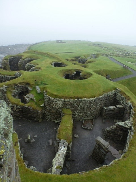 wasbella102:  Jarlshof: looking down into a round house near to Sumburgh, Shetland Islands, Great Britain   The archaeological site at Jarlshof represents over 4,000 years of continual human habitation. The earliest remains are of Bronze Age buildings from around 2500-2000 BC; Iron Age round houses date from between 200 BC and AD 800; a Viking settlement from the 9th to 14th centuries stands towards the eastern side of the site; and finally the castle, the Laird's House, stands in the centre of the site and was converted from a medieval farmhouse to a fortified residence in the 1500s.  Similarly to Skara Brae in Orkney, the Jarlshof site was hidden until a storm in the late 1800s expsed some of the remains. Archaeological work in the 1920s and 1940s/50s revealed the full extent of the site. Here, we stand on the top floor of Jarlshof: the Laird's House and look west over the later Iron Age buildings, larger and more advanced than the earliest round houses on the opposite side. It is easy from here to appreciate the term 'wheelhouse' used for these buildings - built in circular fashion around a central hub with storage areas and small rooms leading off it.