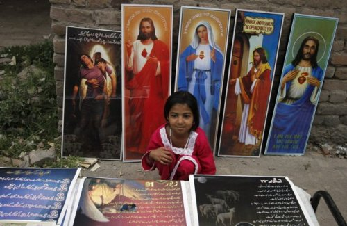 A Pakistani Christian girl sits among religious posters on display for sale in a public park during Easter celebrations in Peshawar. Follow us on Facebook | Twitter or Submit something or Just Ask!