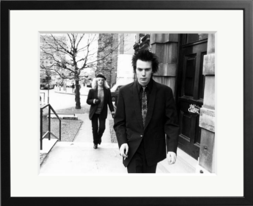 Sid Vicious, bass player for The Sex Pistols, smokes a cigarette while walking up a flight of stairs in front of his girlfriend, Nancy Spungen, in London, England.