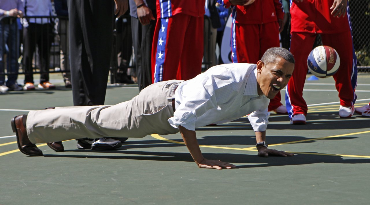 U.S. President Barack Obama does push-ups while playing basketball during the 2012 White House Easter Egg Roll on the South Lawn in Washington April 9, 2012. [REUTERS/Kevin Lamarque] See more Reuters photography