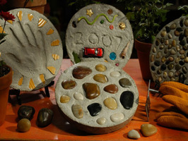 "Pebble Paintings It's a blast from the past with '70s-style rock art that combines color, shape and texture. Cathie Filian and Steve Piacenza are full of crafty ideas guaranteed to rock your world! Planet Earth is the inspiration for amazing pebble paintings, stepping stones receive a personal touch, and paperweights and lucky bamboo bring a Zen presence to any desk. Materials and Tools: 1/4"" thick plywood (cut to desired size)3/4"" thick molding (enough to go around the plywood)sawmiter boxwood puttyputty knifewood embroidery hoops (different sizes to fit the design) small aquarium pebbles (different colors)natural pebblesE6000 gluelarge amount of Mod-Podge or other découpage mediumcraft paintpaintbrushesfinishing nails and hammerpicture hanger Steps: 1. Using a saw and miter box, cut mitered edges into the molding to create a frame for the plywood. Attach the molding to the outside edges of the plywood with finishing nails. 2. Fill any gaps between the plywood and the frame with wood putty. Next, apply a small amount of putty around the perimeter of the plywood where it meets the molding frame and let dry. 3. Paint the frame and plywood interior a color that will match the rocks. Based on the design pattern, paint each of the inside hoops with craft paint and let dry. 4. Place the hoops on the plywood according to the pattern and glue in place. If desired, cut the hoops apart, remove a section and place the hoops in an interlocking pattern with another hoop. 5. Fill the hoops with colored aquarium rocks. Fill the remainder of the plywood base with natural pebbles. 6. Pour découpage medium over the surface of the artwork. Brush the medium evenly over the frame to create a uniform sheen. 7. Let the découpage medium dry flat for 2 weeks. Attach a picture hanger to the back to hang or use flat as table decor. If hanging on the wall, use an anchor to support the weight."