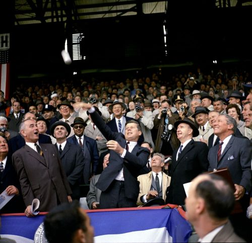 "President Kennedy throws the first pitch of the 1961 baseball season at Griffith Stadium, Washington, D.C. 4/10/1961 Griffith Stadium hosted every POTUS from William Howard Taft to JFK before it was demolished in 1965. Taft was a baseball fan and initiated the tradition of the Presidential first pitch at Griffith Stadium.  As the home of The Washington Senators, the stadium featured a presidential box behind first base.  Also seen in this photo are Vice President Lyndon B. Johnson; Senator Hubert Humphrey of Minnesota; Special Assistant to the President Dave Powers; majority owner of the Washington Senators franchise General Elwood R. ""Pete"" Quesada; Senate Minority Leader Everett Dirksen of Illinois; Secretary of Health, Education, and Welfare Abraham Ribicoff; Associate Press Secretary Andrew Hatcher; Secret Service Agents Gerald ""Jerry"" Behn and John J. ""Muggsy"" O'Leary."