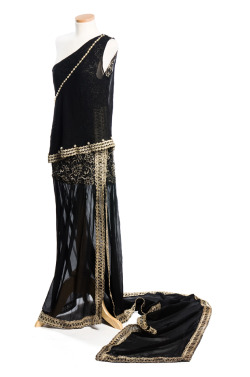 charlestonmuseum:  Black chiffon evening dress with silver lace bodice, c. 1920. The dress has a fashionable low waist and a stunning long train. The asymmetrical neckline is ornamented with applied pearls; the skirt is slit up the side to the lace and is trimmed with silver metallic braid. It was worn by the donor's mother, Ethel Sanford (1873-1924, Mrs. John Sanford), international socialite, or possibly by the donor. The one-shouldered styling and the long train are probably the work of one of the period's top designers, however the dress is unlabeled.