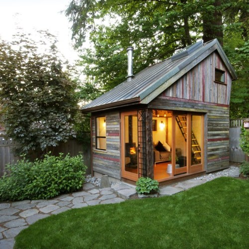 unconsumption:   This charming [154-square-foot] backyard retreat, constructed in less than six months, used salvaged lumber from three Oregon barns, a salvaged copper roof, natural plaster walls and a wood stove. The loft support is exposed, underlining a desire to showcase the beauty of the structural elements.  (via The Backyard House — PortlandOnline) More photos on owner Megan Lea's site here.