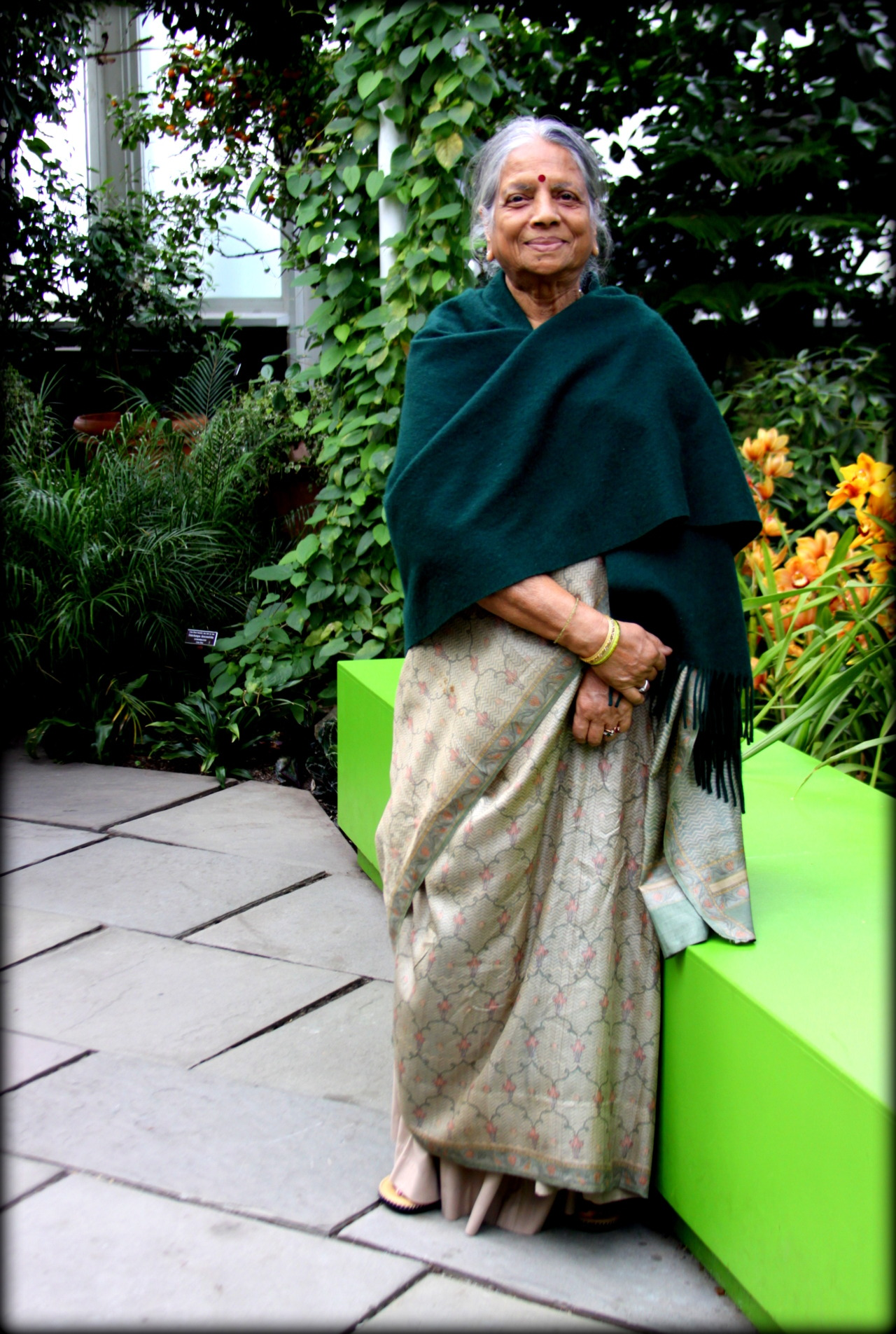bridgeandtunnelgirl:  Indian woman with bindi at the New York's Botanical Garden She looked so beautiful enjoying the scenery, looking at the beautiful orchids, wearing a wonderful lightweight sari and a wrap, the tones of which blended so well with her surroundings and I could not resist asking her to pose for this photo.  Isn't she beautiful! Thanks so much for sharing. ~AR