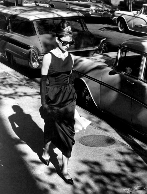 "Audrey Hepburn in Breakfast at Tiffany's (1961, dir. Blake Edwards) (via) ""The ragbag colors of her boy's hair, tawny streaks, strands of albino-blonde and yellow, caught the light. It was a warm evening, nearly summer, and she wore a slim cool black dress, black sandals, a pearl choker. For all her chic thinness, she had an almost breakfast-cereal air of health, a soap and lemon cleanliness, a rough pink darkening the cheeks. Her mouth was large, her nose upturned. A pair of dark glasses blotted out her eyes. It was a face beyond childhood, yet this side of belonging to a woman. I thought her anywhere between sixteen and thirty."" -Truman Capote, Breakfast at Tiffany's (1958)"