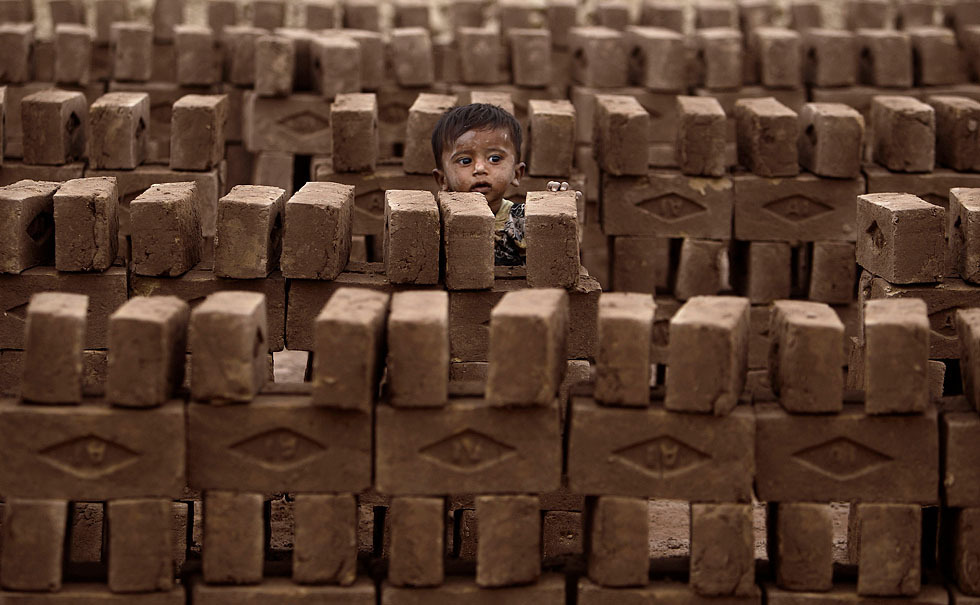 A Pakistani child stands between bricks while his mother, not pictured, works in a brick factory on the outskirts of Islamabad, Pakistan, April 9, 2012. [Credit : Muhammed Muheisen/AP]