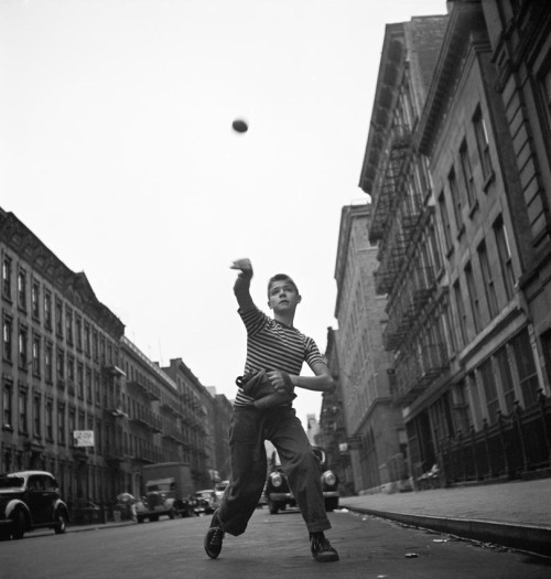 Boy playing baseball on the street, New York, 1948 by Cornell Capa