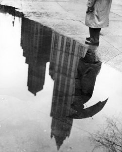 "April 20, 1950: The Woolworth Building reflected in a puddle in City Hall Park. The original caption deemed it ""an eerie reflection of the skyline."" Photo: Arthur Brower/The New York Times"