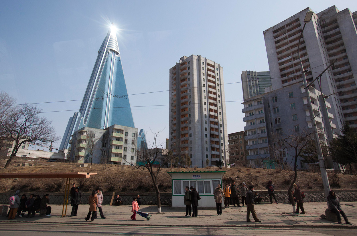 From North Korea Prepares for a Milestone Year, one of 37 photos. The sun is reflected from the top of the 105-floor Ryugyong Hotel, which remains under construction, in Pyongyang, North Korea, on April 1, 2012. The hotel is the largest structure in North Korea, and has been under construction (with numerous lengthy delays) since 1987. (AP Photo/David Guttenfelder)
