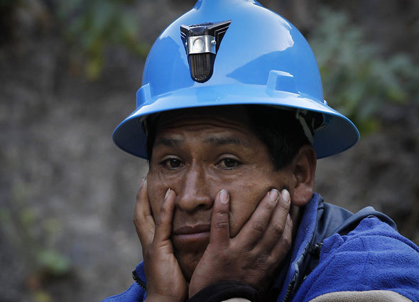 A miner watches rescue operations for fellow miners trapped inside the Cabeza de Negro gold-and-copper mine in Yauca del Rosario, Peru, April 10, 2012. Authorities say nine miners trapped inside the wildcat mine since April 5 are being supplied with sports drinks, soup and food while emergency responders work to free them. [Credit : Martin Mejia/Associated Press]