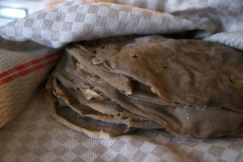 Injera, surdegspannkakanca 10 st5 dl teffmjöl*7,5 dl kallt vattenefter jäsning: 2,5 dl kokande vattenRör försiktigt ut teffmjölet i det kalla vattnet, ta lite vatten i taget så det absolut inte blir några klumpar. Täck med en bakduk eller en bambumatta (som den man använder till sushi) och låt stå i minst två, helst tre, dagar. Ju längre desto syrligare, men i ett hyfsat varmt kök kan två dagar ändå räcka. Det viktiga är att smeten får stå i lugn och ro, rör absolut inte under tiden. Efter någon dag kommer ytan att vara täckt av vatten, men efter tre dagar kan det se ut så här om det jäst på riktigt ordentligt. Efter jäsdagarna, häll försiktigt av eventuellt vatten som stigit upp till ytan. Rör sedan ner 2,5 dl kokhett vatten lite i taget, tills konsistensen är en aning tjockare än pannkakssmet ungefär. Tillsätt lite mer vatten om det behövs, men det här är ett av injerans kritiska moment, och helt och hållet en fråga om känsla. Antagligen tar det ett par gånger innan du hittar exakt rätt. Rör bara inte mer än nödvändigt, då riskerar du att förstöra de fina jäsbubblorna. Låt jäsa ytterligare två timmar. Sedan kommer kritiska moment nummer två: hetta upp en stor torr stekpanna till medelvärme (pröva några olika pannor för att se vilken som funkar bäst, jag har en teflon som det funkar jättebra med, men en som inte funkar alls! Och en gjutjärn som går helt ok. Det viktiga är att den är helt fri från fett, eftersom ytan inte ska bli det minsta krispig utan mjuk) och häll i lite smet. Tilta pannan så att smeten fördelas jämnt i ett tunt lager och vänta någon halvminut tills bubblor börjar synas på ytan. Täck med lock (det underlättar om det är av glas) och låt injeran steka tills kanterna börjar korva sig och all smet stelnat (obs! injera steks bara på ena sidan, den ska alltså inte vändas som en pannkaka).Kritiska moment nummer tre: lossa injeran försiktigt från pannan, du hittar din egen teknik men enklast är nog att peta lite längs kanterna med en stekpanna och sen l