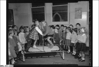 Photograph of two children using the trampoline watched by others at the Pre-School Kindergarten on 15th May 1963, Mount Gambier