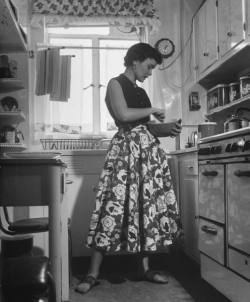 Career girl and hostess Joan Wilson cooking in the kitchen. Nina Leen, 1950.