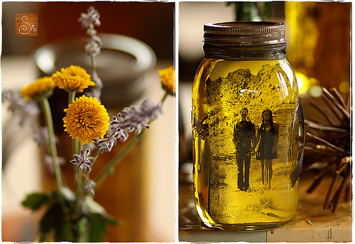 Pictures in Mason jars. Perfect for centerpieces for each table.