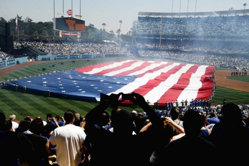 A 50th anniversary at Dodger Stadium, with a sober undertone: Hundreds of LAPD officers provide security at the stadium, a reminder of the opening day beating last year of Giants fan Bryan Stow. Fans have mixed feelings about the police presence. Photo: The American flag is unfurled during the national anthem on opening day at Dodger Stadium. Credit: Gary Friedman / Los Angeles Times