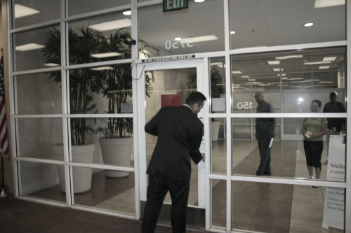 "Photo: Riverside branch Well's Fargo bank manager/Vice President locking *in* 6 concerned students/faculty/community members while locking *out* his own customers. Press Release:  Thanks everyone for coming out and supporting the statewide… release of the ""Report on the 1% in CA"" in Riverside today. We had a good press conference with testimony from students and community members, even after the police shut down our microphone for not having a permit to speak in a public space. Afterward the police followed us as we visited a local Wells Fargo branch and presented the manager with a copy of the ""Report on the 1%"" and a letter demanding Wells shareholders and executives support the ""Solutions for the 99%"" agenda, stop engaging in unethical business practices that are devastating our communities and divest from companies like the GEO Group and Corrections Corporation of America, who profit from incarcerating predominantly people of color and low-income community members. When we asked the bank manager to set an example and sign the pledge he locked the doors to the bank and let us know we were a ""potential threat"" to staff and bank customers. There were six students, workers and community members who, all things considered, were being exceedingly polite with this gentleman and at no point constituted any threat to anyone in that building. Conversely, the presence of Wells Fargo and other tax-dodging corporations who actively and knowingly created the current socioeconomic crisis with their unethical business practices present a very real and ongoing threat to our communities, and that is what we were there to demand accountability for. The bank manager was under the false impression that Wells Fargo's ""philanthropic"" donations and ""community volunteerism"" were adequate compensation for the egregious and lucrative predatory lending, unjust foreclosure and similar practices his employer and many of their associates engage in. The branch manager's name is Samuel Robles and can be contacted at 951 782 2670 or samuel.l.robles@wellsfargo.com . Please feel free to send him a polite phone call and email letting him know how you feel about Wells Fargo's predatory lending and foreclosure practices and that you expect him to set an example in this community by signing and actively supporting the ""Solutions for the 99%"" pledge and agenda.  Brownanon[@]gmail[dot]com for more information."