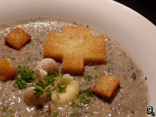 gourmetgaming:  Minecraft – Mushroom Stew  Is it a stew? Is it a soup? Not even Notch seems to be sure. What we do know is that mushrooms are awesome. Why, you ask? Because mushrooms are the very foundation of the gaming industry. Without the iconic '1-UP', perhaps gaming wouldn't have become as popular as it is today. It's a sobering thought, but from Mario to Minecraft, mushrooms have appeared in innumerable titles across the years. I'm also a personal fan of the fungi, as a vegetarian they feature a lot in my diet. They're incredibly delicious, but mushroom soup is probably one of the most foul things you can ever taste, especially when it comes from a can. So change your mind, and follow in the footsteps of gaming heroes by enjoying some real, fresh mushroom stew. (No Mooshrooms were harmed in the making of this recipe). This recipe serves 4. What you will need: A large and deep frying pan/skillet, kitchen towel and a small pot. For the Croutons: Olive Oil Salt 4 Slices White Bread For the Mushroom Stew: Olive Oil Truffle Oil (Optional) Salt & Pepper 300g / 4 Cups Mushrooms (Chopped) Portabello Pink Oyster Yellow Oyster Shimeji 1 Tablespoon Butter 1 Small White Onion (Chopped) 1 Clove Garlic 500ml Vegetable Stock (Or use 250ml Vegetable and 250ml Mooshroom/Beef stock) 1 Tablespoon Fresh Thyme (Chopped) 1 Tablespoon Fresh Parsley (Chopped) 110ml / ½ Cup Single Cream Making the Croutons: Using a sharp knife, cut out the shape of the pixelated mushroom. You can use this image as a template. Cut out some squares too and set aside. Heat a few tablespoons of olive oil and a dash of truffle oil in a large frying pan. Add a little salt once heated, then carefully lay the bread shapes into the pan. Once they are golden on one side, flip them over. Remove the croutons from the pan when crisp and lay them on some absorbent kitchen towel to drain any excess oil. Set aside for garnishing later. Making the Mushroom Stew: Heat the olive oil in a deep frying pan on a medium high heat. Once hot add the mushrooms and fry for one minute. Next, add the butter, onion and garlic and stir. Season with a little salt and pepper, drop in the thyme and allow to cook. Once the moisture in the pan has reduced and is almost gone, add the stock. Bring it to the boil, then allow the soup to simmer for about 5 minutes. Once simmered, pour the soup into a bowl and blend for a few minutes. You can blend it to be very smooth, or leave it a little chunky – whichever you prefer. Once blended, pour the soup into a clean pot and warm through. Add the cream and some parsley and stir well. Serve the soup up, and garnish with the croutons, some thyme, parsley and a drizzle of truffle oil.  I was really pleased with how this turned out, and by some stroke of fate I managed to pick mushrooms at random in the store that just so happened to be perfect for soups! There's a great depth of flavour that's light and warming, and the croutons add a delightful contrast in texture and taste. I will make a warning though, this stew/soup certainly wont be for everybody. I think you'd probably have to love mushrooms to like this. And I mean really love mushrooms. You'd have to be, like, a spore away from being one yourself – or maybe just a fun guy or gal (that's right, I went there). For those of you that do like it, however, just make sure not to gobble the bowl while you're at it.