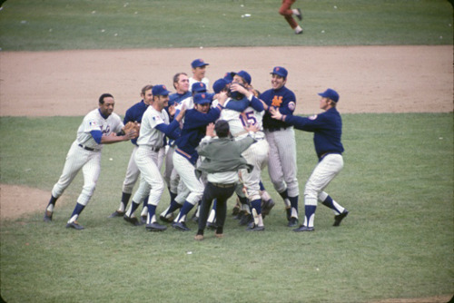 "Happy 50th Birthday, Mets! This week marks the 50th anniversary of the inaugural New York Mets season. The Mets played their first major league game on April 11, 1962, which makes them officially a 50-year-old franchise. When I was growing up in southern Connecticut, which was kind of an honorary extension of New York City, the Mets were newbies not to be taken seriously. They were a team made up of has-beens and peculiar draft choices to fill a National League void left in America's biggest city by the departure of the Dodgers and Giants to the West Coast. They weren't going to convert any Yankee fans. Their first couple of seasons, as anyone with a working knowledge of baseball knows, were disastrous. The 1962 Mets still hold the record for the most losses in a season - 120! They probably could have added two more losses to that column, but those rained out games were never made up. The Mets had a few things going for them, though. They were managed by the now-doddering Casey Stengel, who a decade earlier had been the genius manager of the Yankees and their 5 consecutive World Series titles (1949-1953), followed by two more in 1956 and 1958. Revered as the Yankee skipper, by 1962 he was ""washed up"" in Yankee-land, but took his job with the Mets in stride. He talked all-things ""Metsie"", even when he was confusing his players names and being misquoted as saying ""Can't anybody here play this game!?"" The Mets were owned by Mrs. Joan Payson - the first woman to ever purchase a baseball franchise with her own money. Gil Hodges, a huge star with the Brooklyn Dodgers in his prime, was brought back from the West Coast to play first base. And, the Mets, in addition to their flashy orange and blue colors, had the best theme song (still do). Sportswriters, gamblers and champions of the underdog (many of whom seemed to live in the newly minted suburbs of Long Island and southern Connecticut) loved the Mets. They made a good story. When they won, they won big. They were proof that not everyone in the New York metro area wants a ""sure thing"" all the time (the Yankees). In 1969, after years of ""cellar dwelling"" and never finishing better than second to last place, a miracle occurred. The Mets won their division, the league championship and the World Series in 5 games over the Baltimore Orioles! They were the Miracle Mets, yes indeed! My father went to one of the World Series games that year. He's a St. Louis Cardinals fan, but at World Series time, if the Cards aren't in it, he roots for the National League team. This meant that he was pulling for the Mets. Whenever I see this photo, I think of my Dad's good luck at scoring a ticket to this historic World Series, even though it was Game 4 he went to, not the miraculous Game 5. As a lifelong Met fan, this has always been one of my favorite photos of the team. No doubt taken by a professional photographer just moments after the Mets win the World Series, it looks like it was snapped with someone's Instamatic. It perfectly captures what I remember about all of the Mets' big games at Shea Stadium. Hotdog wrappers on the field, a crazed fan (or two) caught up in the pandemonium (note the one in the rust-colored pants coming in from the outfield), the sheer unbelievability of it all. Guess what, guys? To be a real winner, you have to know what it's like to lose. Note: If you know the real source of this photo, please let me know. I'd like to give credit to the photographer and maybe find out more about their experience of taking such an amazing shot."