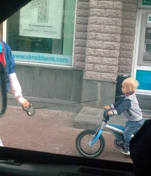 Woman Uses Leash to Pull Kid on Bike   I'll just wrap this rope around his neck and balance him on two wheels. What's the worst that could happen?